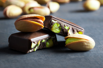 Broken and dark Pistachio Chocolate on black wooden rustic backdrop, composition of pistachios great for healthy and dietary nutrition. Concept of nuts