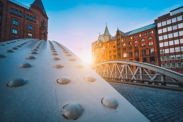 Perspective of iron arch bridges in historical warehouses in Speicherstad district in Hamburg, Germany. Backlit sun light flares