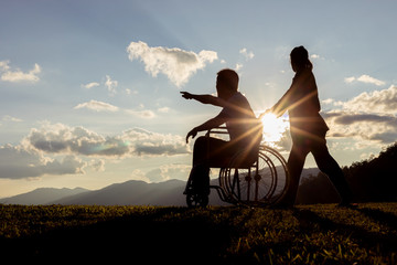 Disabled handicapped young man in wheelchair with his wife at sunset.