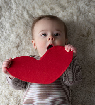 Cute baby boy holding red heart