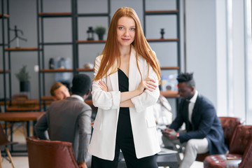 Woman in white blazer with red hair posing look at camera, elegant and modern suit. Attractive...