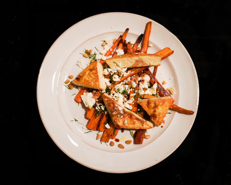 A low FODMAP dinner of roasted carrots, goat cheese, tofu, pine nuts and dill  on a white plate isolated on a black background