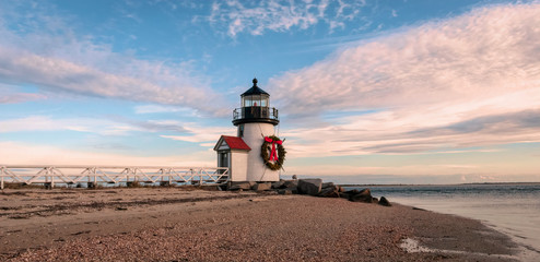 Brand Point Lighthouse, located on Nantucket Island in Massachusetts, decorated for the holidays with a Christmas wreath and crossed oars.  Beautiful clouds surround the lighthouse.