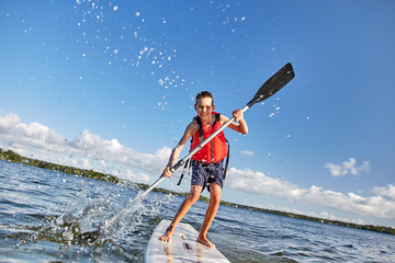 happy boy paddling on stand up paddleboard. cheerful child having fun on water. Summer vacation leisure activity Wall mural