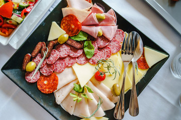 Close up on antipasto platter appetizer cold meat plate slices ham salami cheese decorated with rosemary mint cherry tomato and olive on the table high angle view
