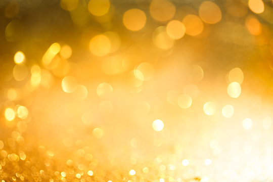 Abstract bokeh of glowing yellow lights and sparkling gold glitter background or wallpaper