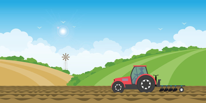 Farmer driving a tractor in farmed land on rural farm landscape hill background.
