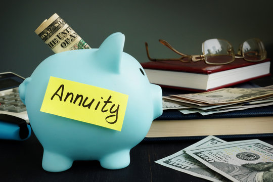 Annuity written on yellow sheet and piggy bank with money.