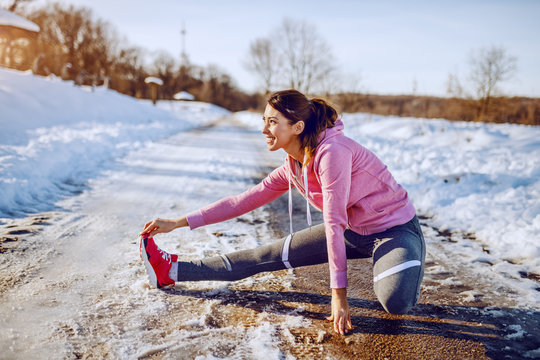Side view of beautiful caucasian woman in sportswear and with ponytail stretching leg on country road. Winter time. Outdoor fitness concept.