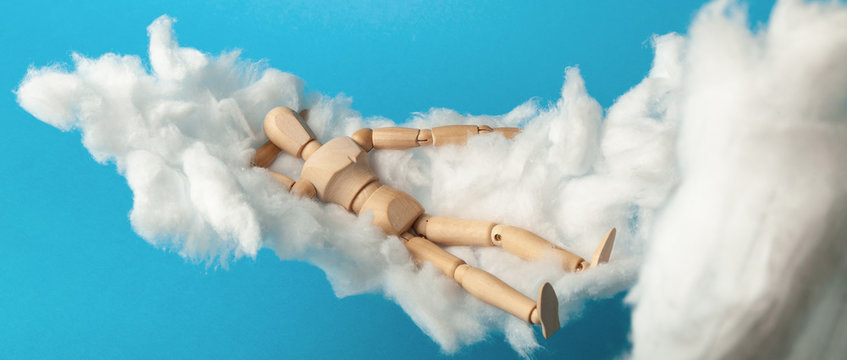 Toy man sleep on fluffy cloud. Freedom and relaxation.