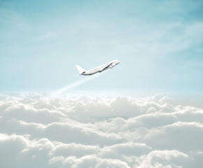 Wall Mural - Airplane flying over the white clouds