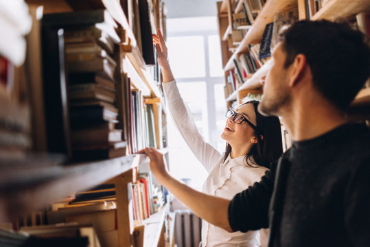 people, knowledge, education and school concept - happy student girl and the guy choose books in the old library