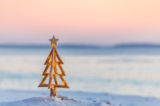 Christmas tree with fairy lights on the beach in summer