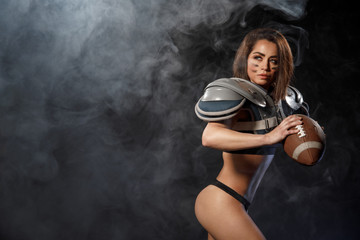 Sexy young quarterback girl with ball in smoke. American football