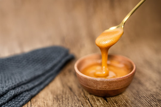 Manuka honey from New Zealand dripping from golden spoon in wooden bowl showing texture of natural healthy organic raw food.