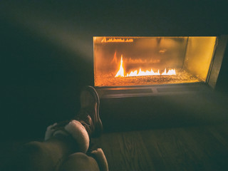 After ski resort woman wearing winter boots sitting by gas bio ethanol fireplace at night cozy fire place with flames glowing in the dark.