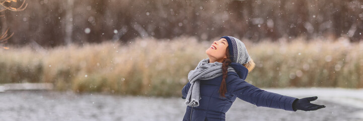 Winter snowing happy Asian girl with open arms enjoying snow fall falling snowflakes wearing cold...