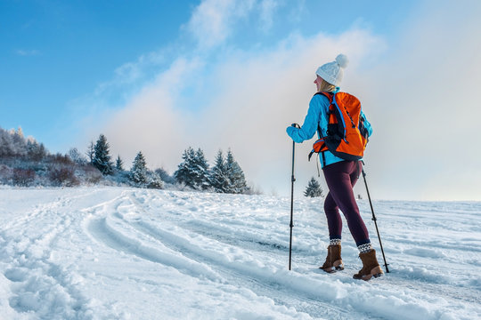 Happy woman tourist walking on the snowy trek on the peak of mou