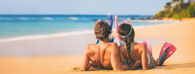 Fototapeta Beach couple relaxing on summer honeymoon vacation with snorkel equipment. People lying down on golden sand at sunset with diving mask, flippers sun tanning enjoying travel holiday lifestyle. obraz