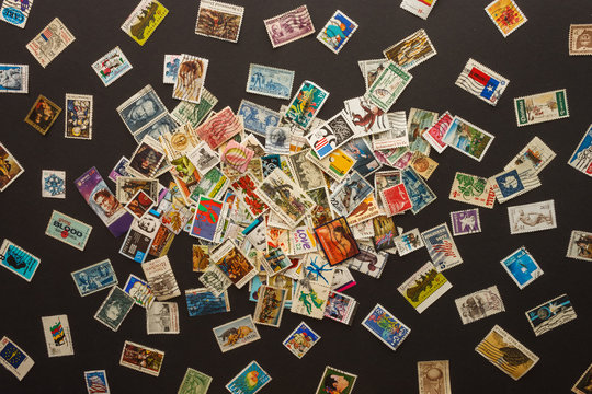 Various old postage stamps scattered on a dark background