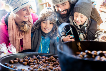 Family on Christmas market eating sweet roasted chestnuts