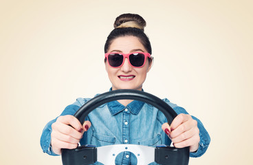 Happy young girl in sunglasses drives a car while holding a steering wheel, front view, auto concept