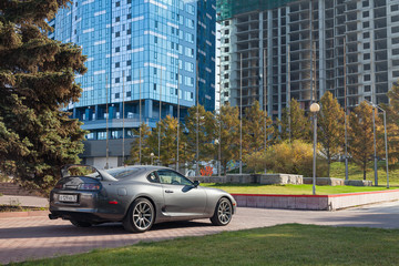 A rare Japanese sports car in the back of a Toyota Supra coupe in gray with a spoiler in park of city near trees with yellow leaves, green grass and modern buildings