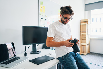 Photographer with camera sitting on desk in studio, office
