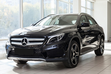 Black Mercedes Benz Gla class 2016 year front view with dark gray interior in excellent condition in a dealership with white walls