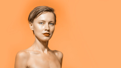 Image of young pure beautiful gentle woman standing naked isolated looking camera over orange color background.  Spa, skincare and wellness