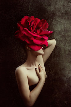 Strange fine art concept. The body of a woman, her head is a red rose.
