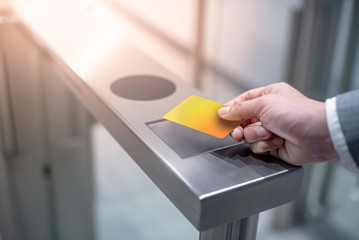 Businessman hand with business wear using yellow smart card to open automatic gate machine in office building. Working routine concept