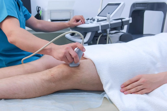 Doctor makes ultrasound of knee joint to man using ultrasound scanner in clinic, closeup leg view. He runs ultrasound sensor over man's leg, working on scanner panel and looking at screen in hospital.