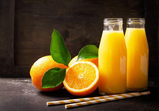 bottles of fresh orange juice with fresh fruits