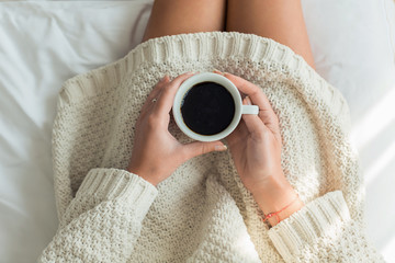 Overhead view of woman holding cup of coffee in her lap