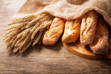 fresh bread with wheat ears on a wooden background