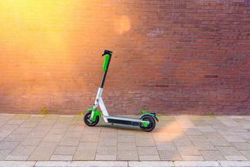 E Scooter vor einer Ziegel Wand im Sonnenlicht