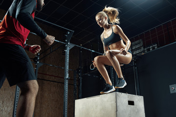Man and woman crossfit workout Fitness woman doing exercises with help of a personal trainer in a crossfit gym Trainer helping girl on her workout routines. Sporty girl  box jump workout at the gym