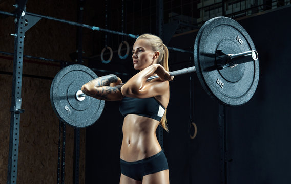 Strong young woman exercising with barbell in a gym Muscular caucasian woman using curved barbell at fitness club Girl lifting heavy weights Shot of a strong woman with muscular abdomen in sportswear.