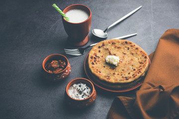 Aloo Paratha / Indian Potato stuffed Flatbread with butter on top. Served with fresh sweet Lassi,...