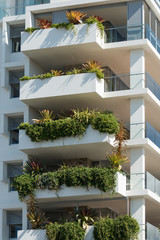 Tall white building with lush green plants