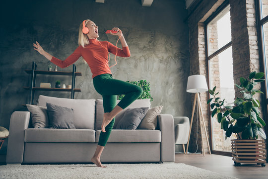 Full body low below angle view photo of pretty lady holding telephone listening song modern orange earphones dancing singing loudly wear casual outfit living room indoors