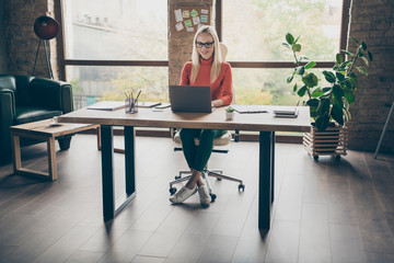Full size photo of positive woman worker sit table use laptop work on start-up strategy type wear...