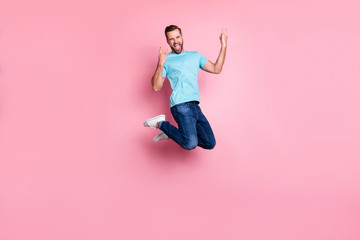Deurstickers Hoogte schaal Turned full length body size photo of crazy insane man showing double rock horned fingers sign screaming in jeans denim jumping isolated pastel color background