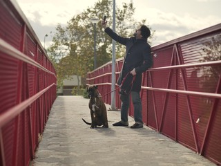 Man with black coat and beard makes a picture with a boxer dog on a red bridge in a park on a cloudy autumn day