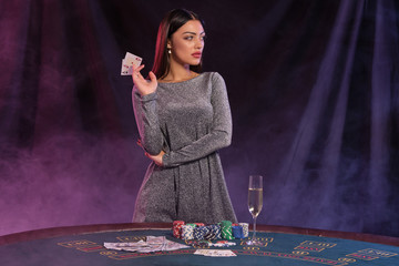Woman in gray dress showing cards, posing at playing table in casino. Black, smoke background with colorful backlights. Gambling, poker. Close-up.