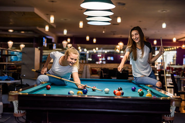 Happy and excited women playing billiard together
