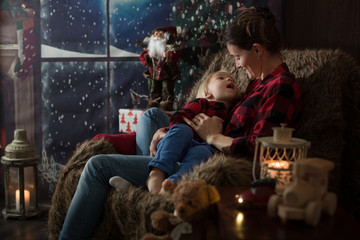 Beautiful young mother, hugging her toddler boy, sitting in cozy chair on Christmas