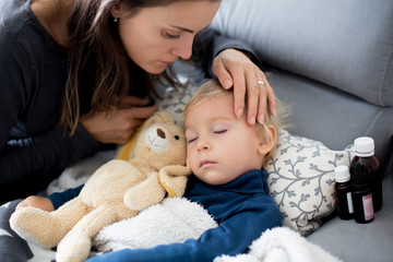 Blond toddler boy, sleeping on the couch in living room, lying down with fever