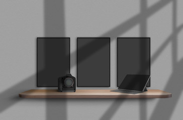 Camera and tablet on wooden shelf, suspended from gray wall with shadows from window on it. Three blank banners hanging above it. Mockup. Close-up.